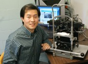 Xiaofei Fan, a post-doctoral fellow at MU, sits next to the computerized binocular infrared pulillography device, a machine that measures the time that the eye takes to react to a flash of light.